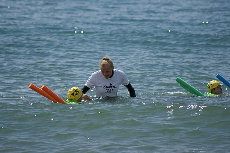Jessica Davies teaching a young swimmer in the sea